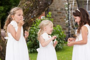 Group Of Bridesmaids Blowing Bubbles In Garden