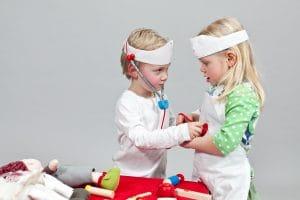 Junge und Mdchen spielen Arzt