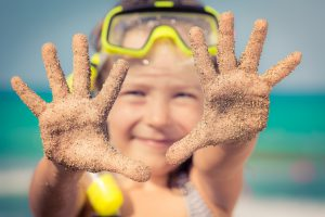 Happy child playing on the beach. Kid showing sand on hands. Summer vacations concept